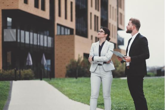 image of a male and female looking at an apartment building
