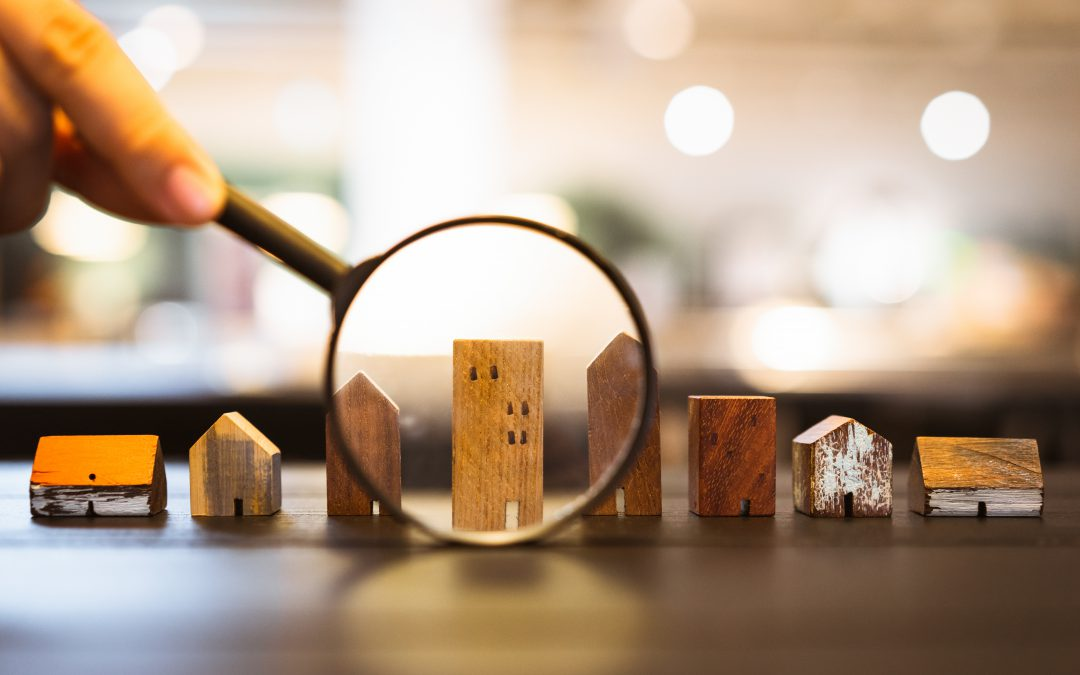 Hand holding magnifying glass and zooming in on a multifamily building, real estate concept.